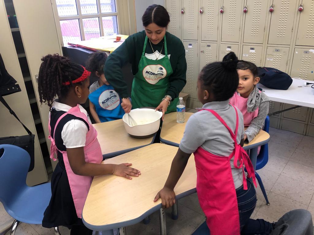 teacher showing children cooking