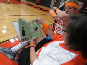 Diane Knight reads up on how to play basketball before the TK Battle of the Buildings games.