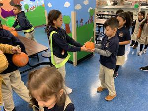 girl handing pumpkin to little boy