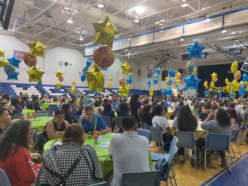 family and friends sitting in the gym decorated with blue & gold balloon stars and other balloons