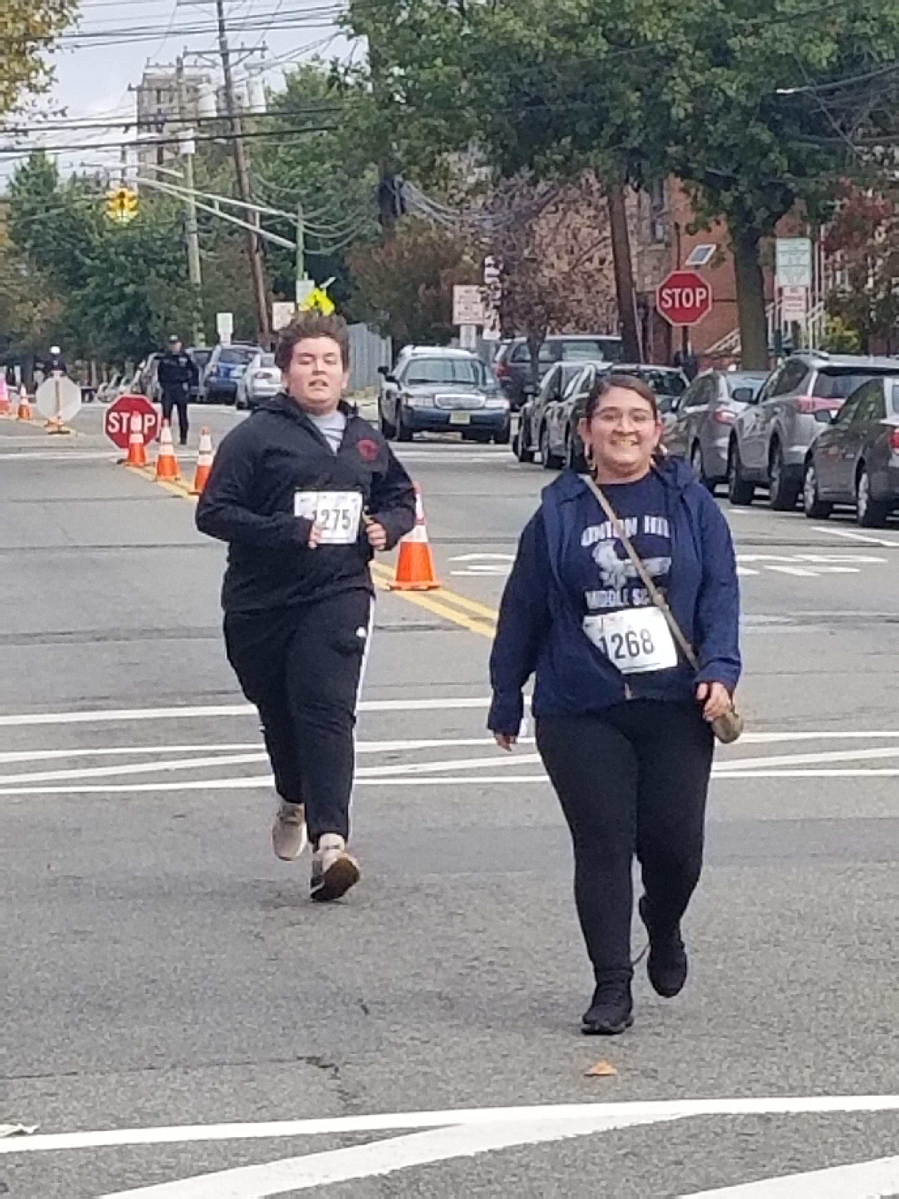 UHMS students one boy running and a girl walking