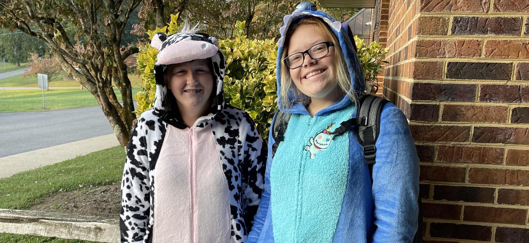 Two students wear pajamas outside a school.