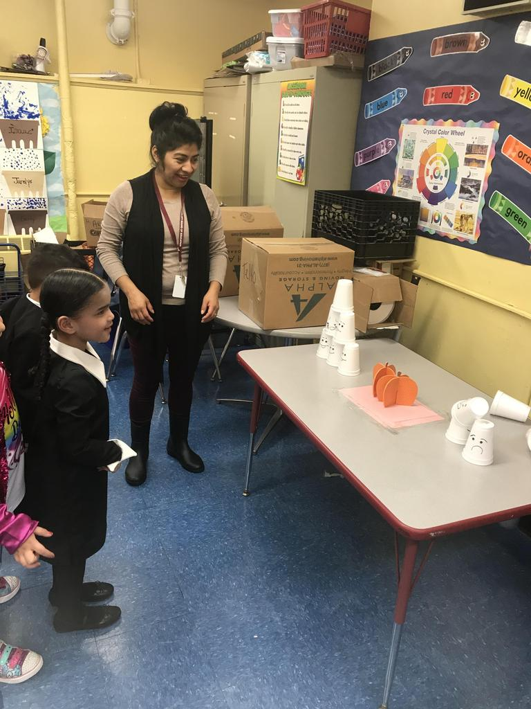 little girl dressed as Wednesday knocking down styrofoam cups on a table