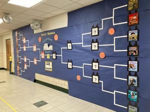 A hallway bracket display keeps track of the winning book titles.
