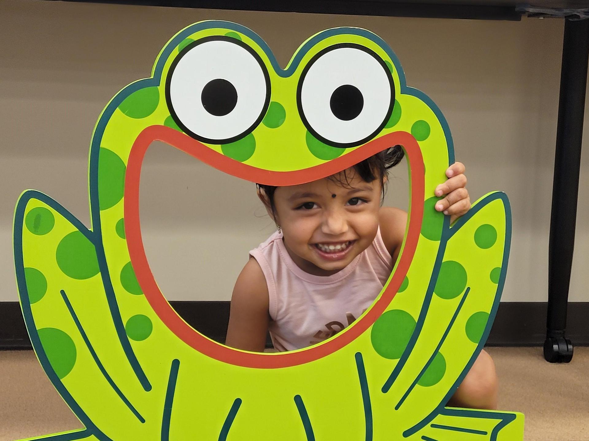 Little girl hides behind frog toss game
