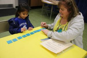 Ms. Cipriano playing a game with a kindergartener.