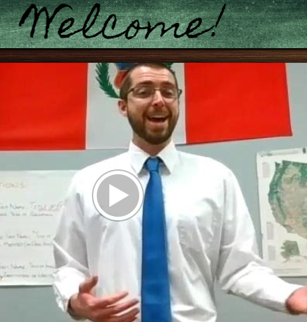 teacher with a tie in front of his classroom wall with flags