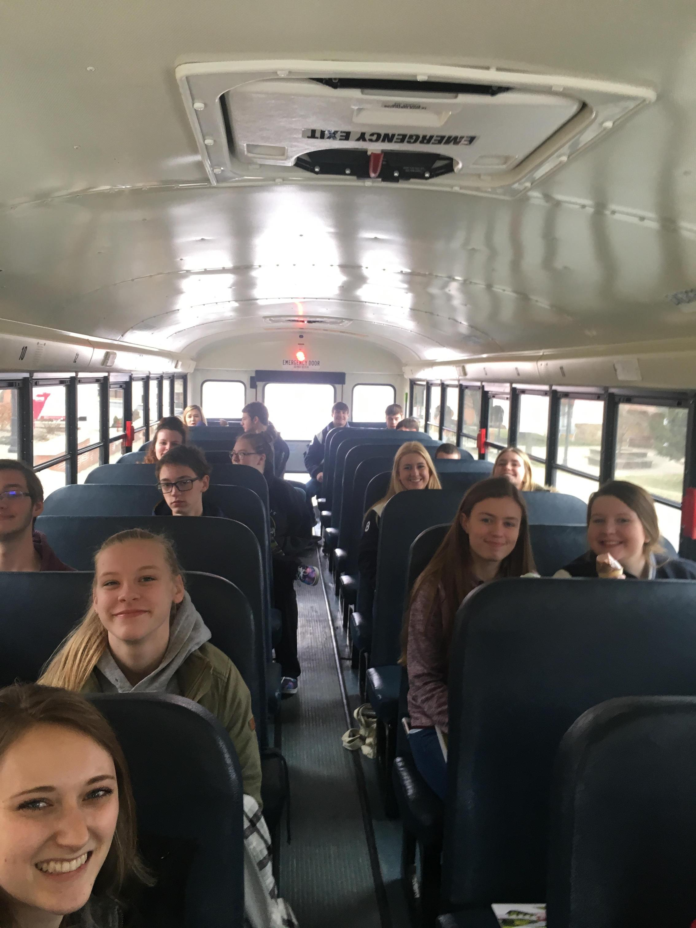 students on a school bus after college tour