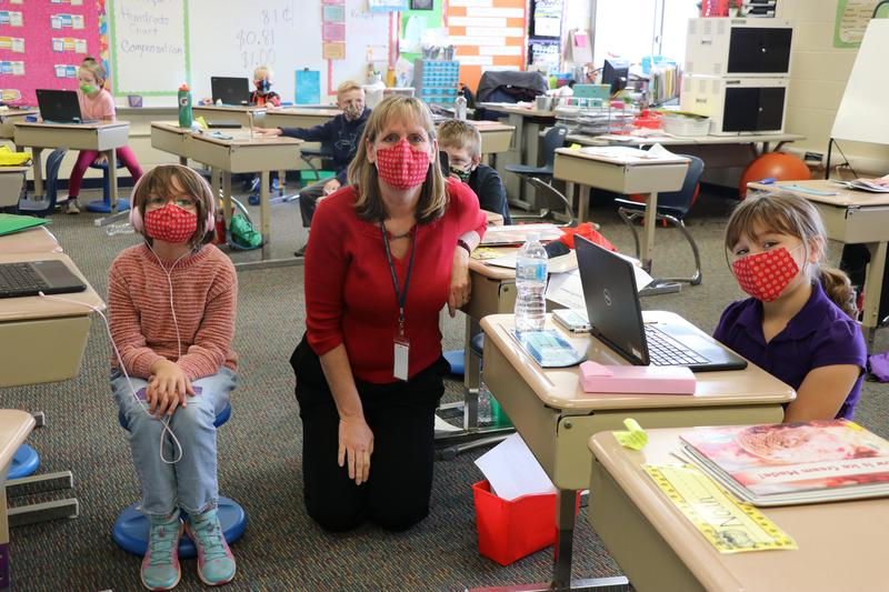 Mrs. Reifert with two students, all wearing matching red masks.