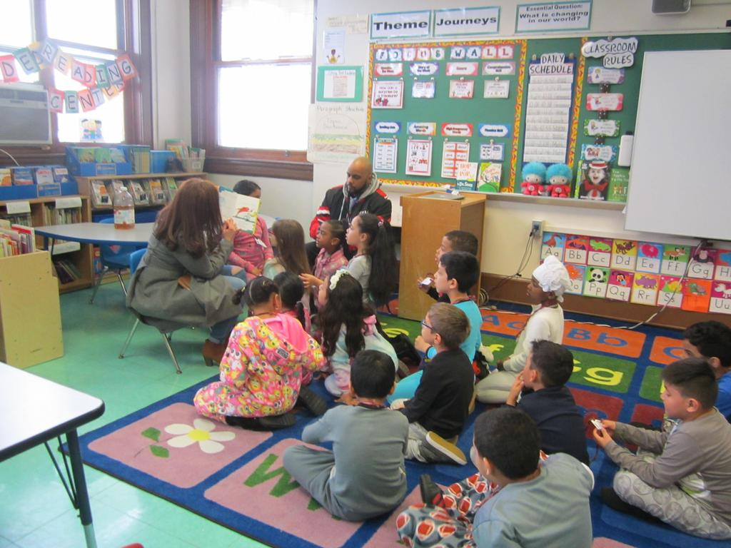 parent reading a dr. seuss book to the class wearing pj's