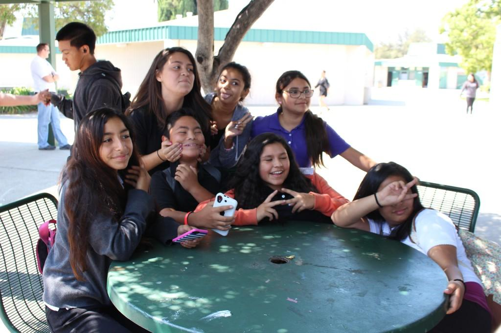 several students pose for a picture while they surround a green table