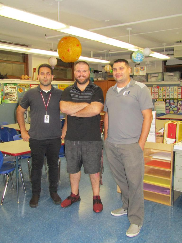 mr. blake, mr. petrovich, and another male teacher posing for the photographer