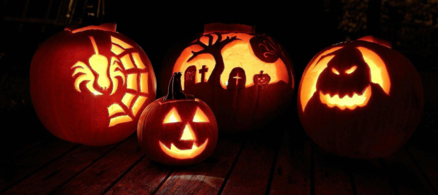 4 pumpkins carved one with spider, graveyard, ghost, smiley face