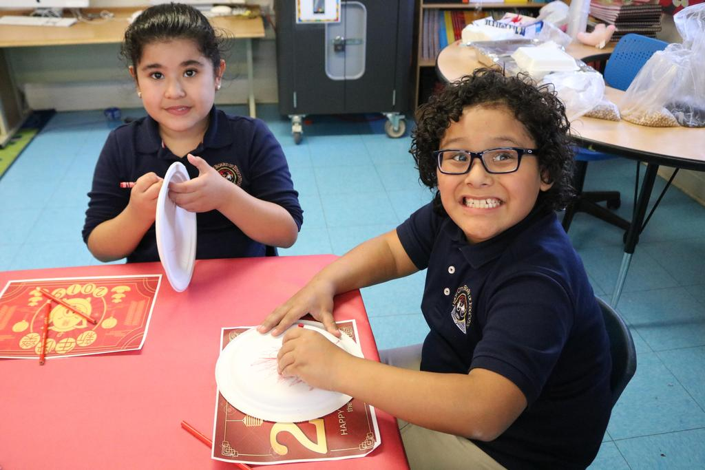 2 kids smiling while coloring their paper plates with red crayon