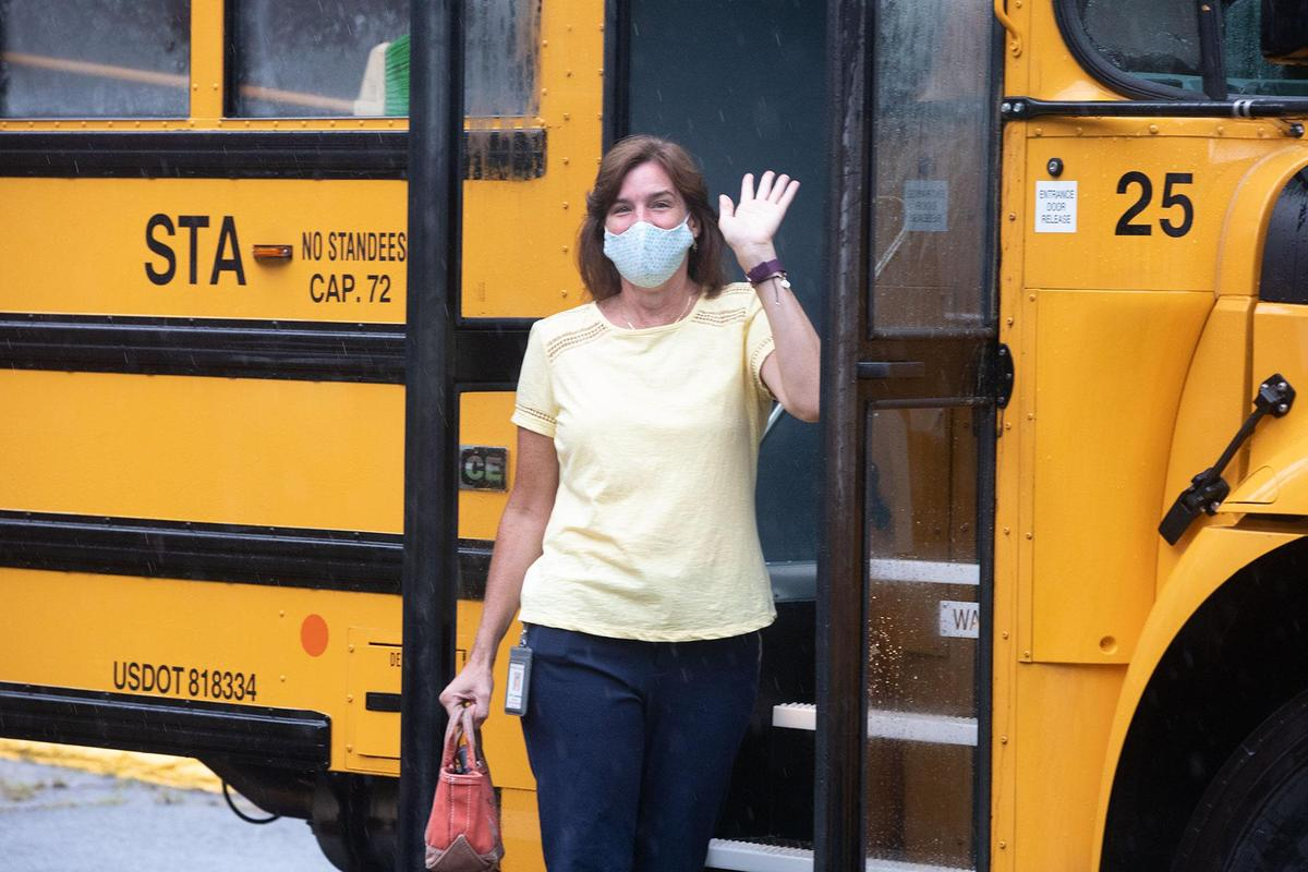 Paraprofessional waving in front of a school bus
