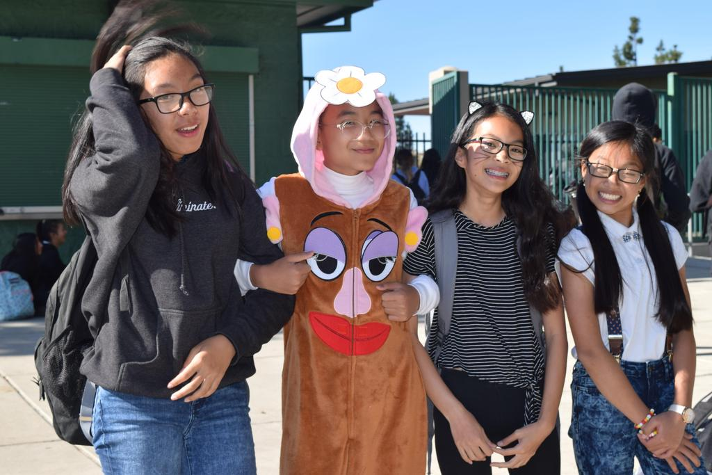 A group of students posing for a Halloween picture. One student is dressed as Mrs. Potato Head.