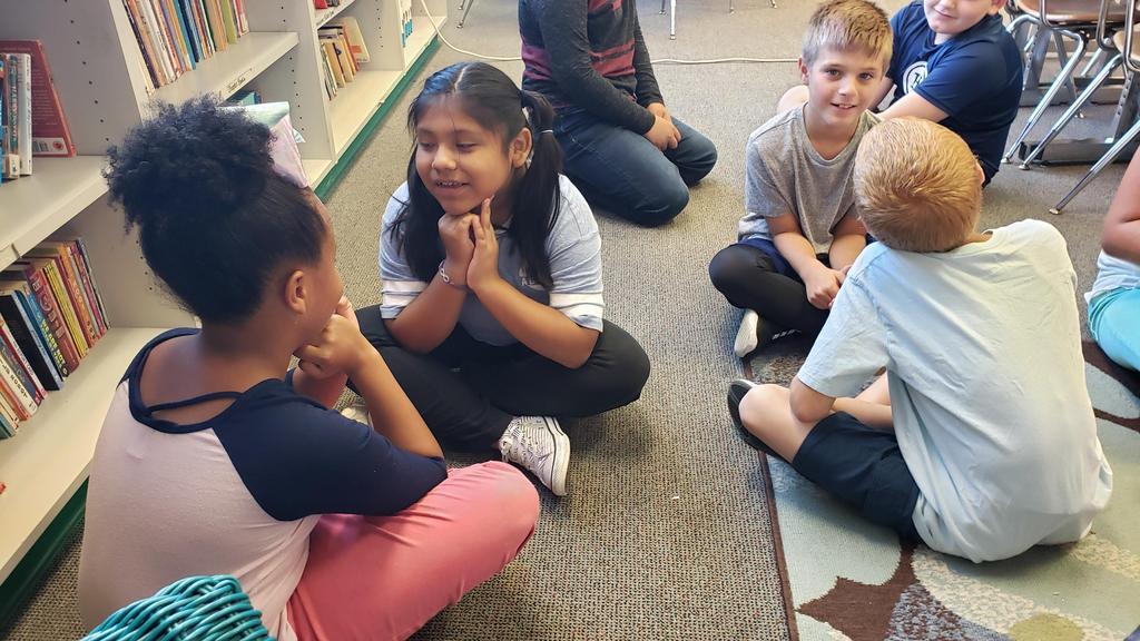 students sitting crisscross in classroom