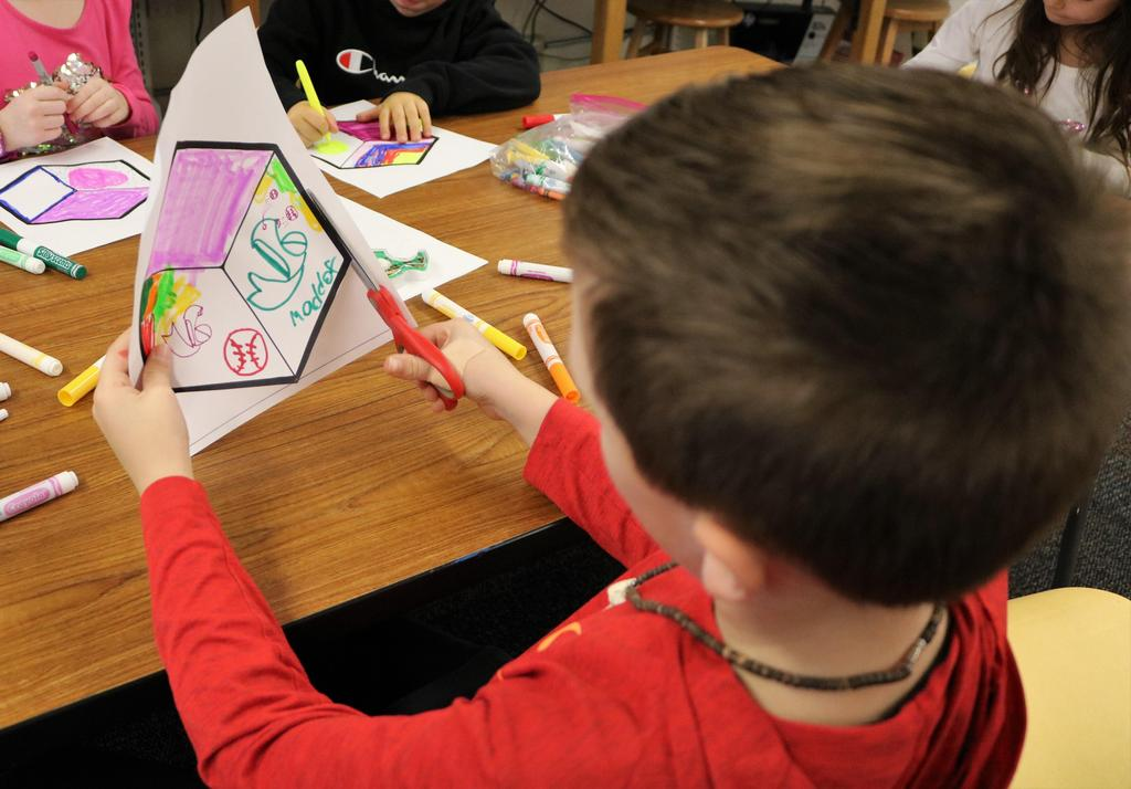 Photo of back of student cutting artwork out as part of collaborative street art project for STEAM Day.
