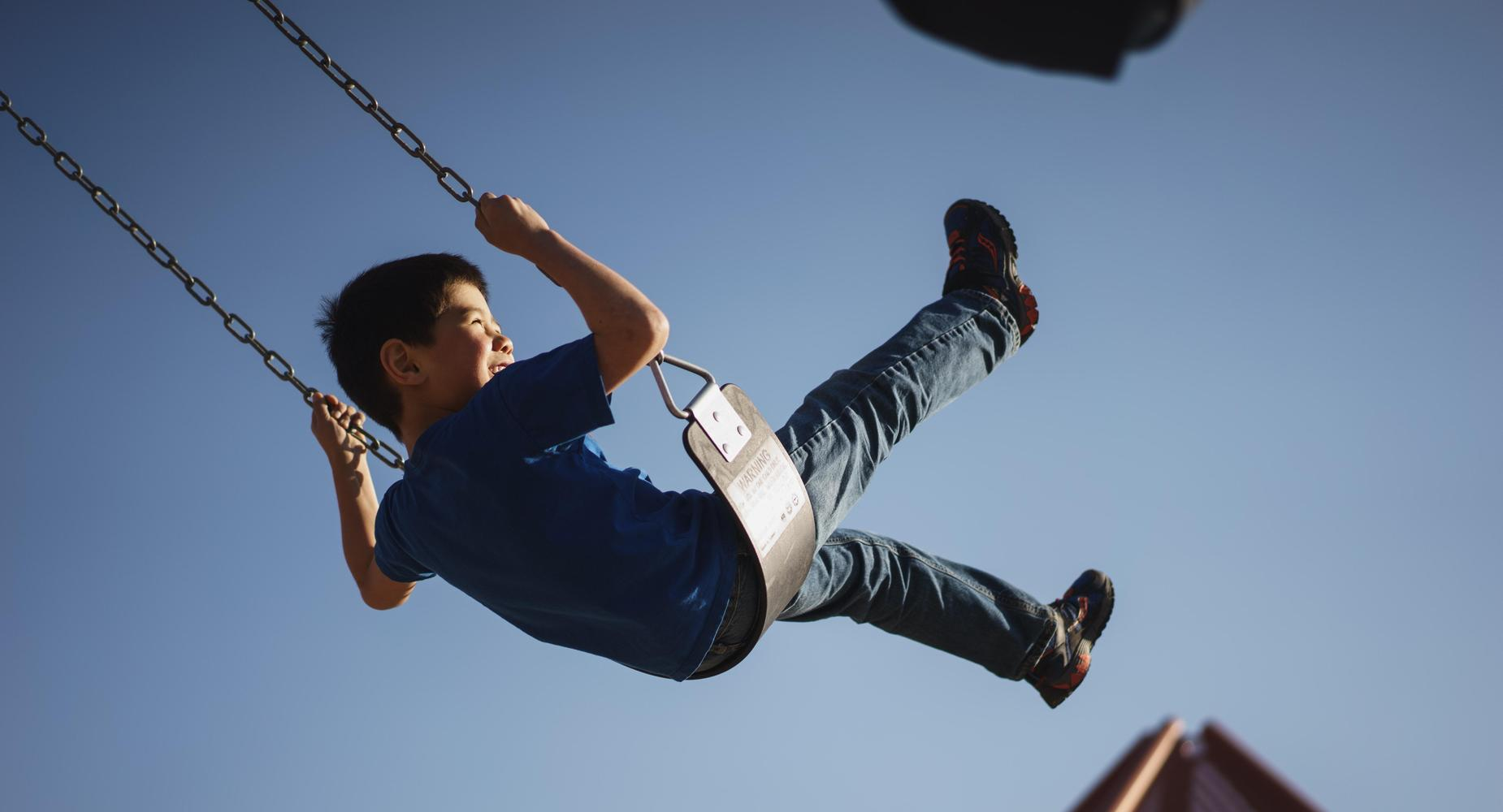 A smiling boy swings into the air, his feet kicking against a blue sky