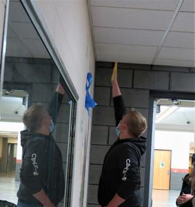 A senior reaches high to leave his handprint on the wall.