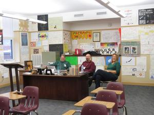 photo of three teachers behind a desk laughing