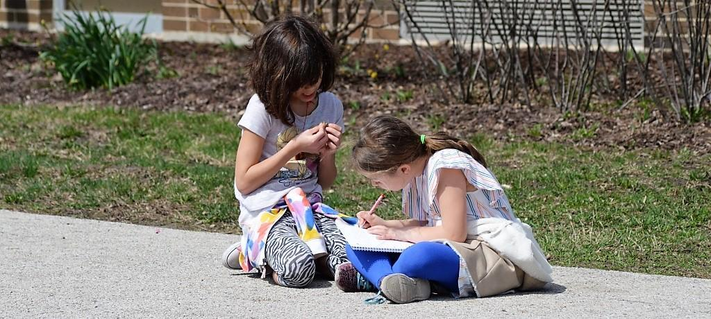 Girls working on assignment outdoors.
