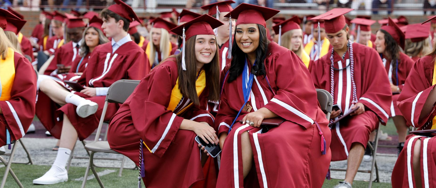 two girls in maroon cap and gown sit in front row smiling at graduation outdoors