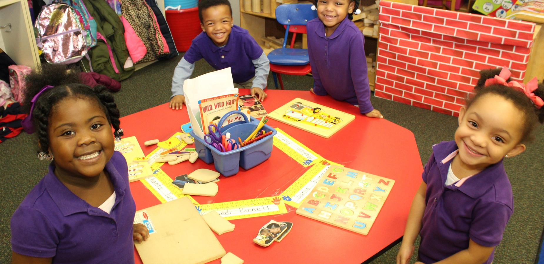 Four young children standing around a red table smiling as they work on puzzles.