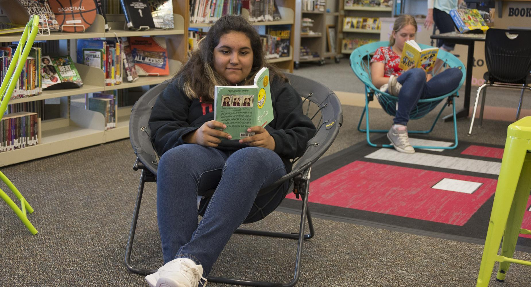 Girl reads a book in the library