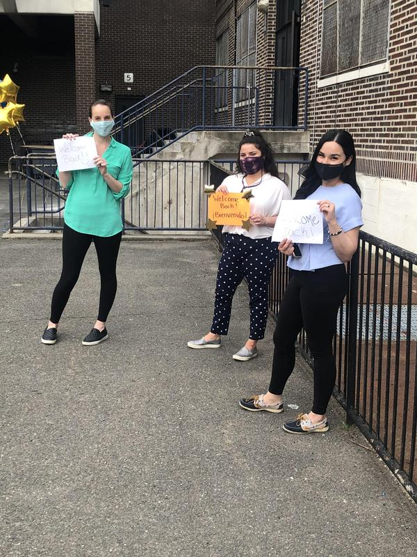 three teachers holding welcome back sign outside school