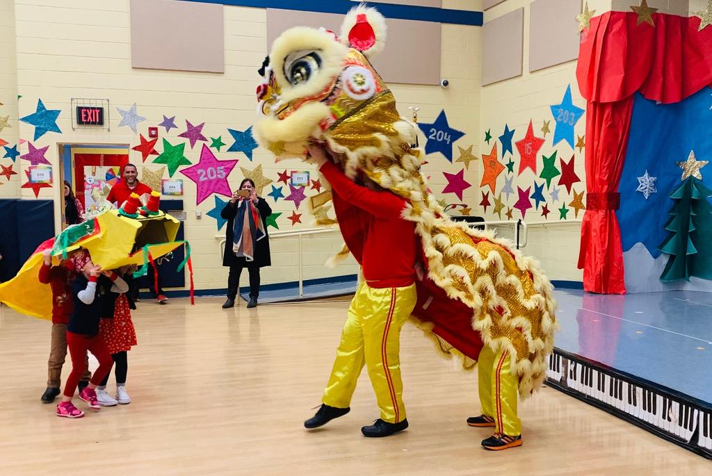 Chinese dragon performers next to the students who created their own dancing dragon face to face