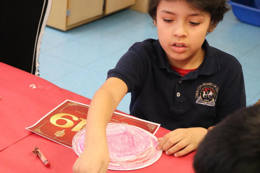 boy finishing coloring his plate