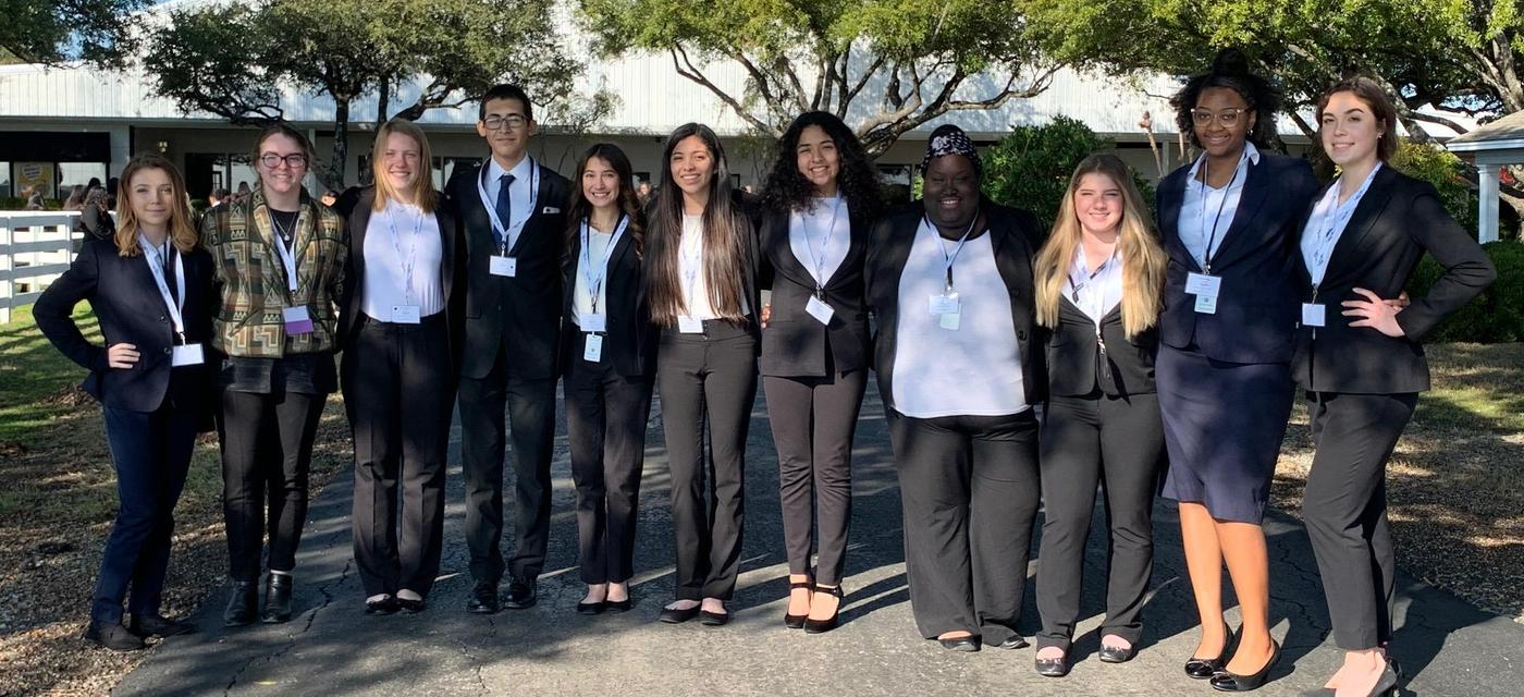 11 HOSA students pose together in suits