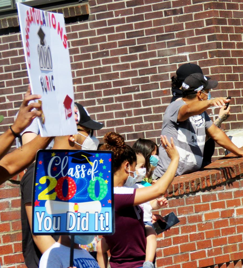 Residents waving and holding signs