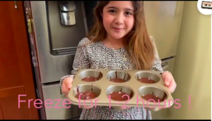 Girl holding up cupcake pan with batter