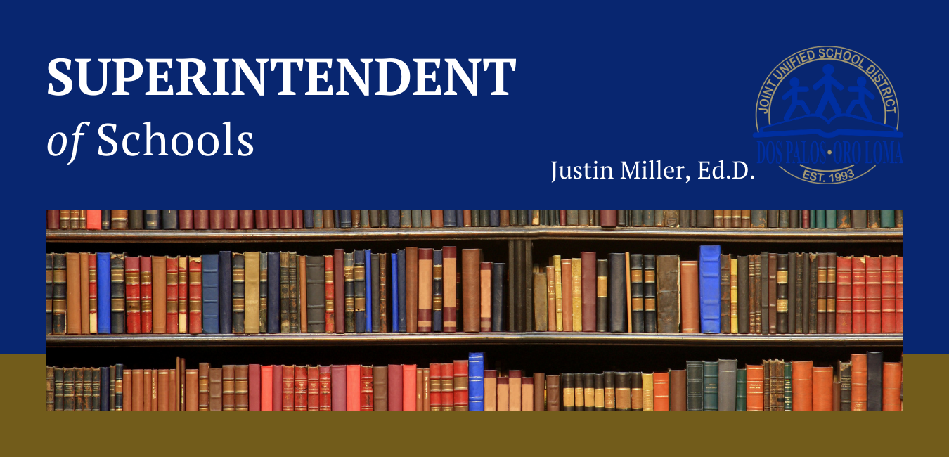Blue and gold, books on shelves, Superintendent of Schools, Justin Miller, Ed.D. caption