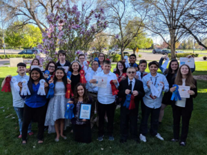 Group photo of speech and debate championship team with ribbons.