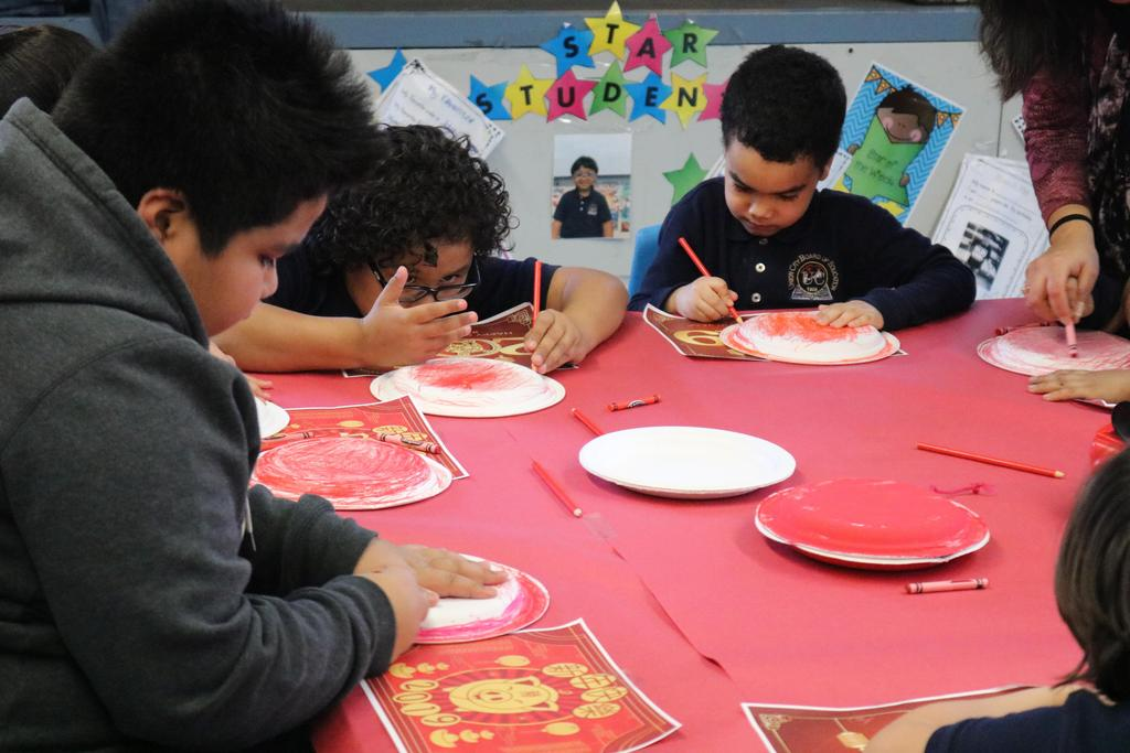 kids smiling while coloring their paper plates with red crayon
