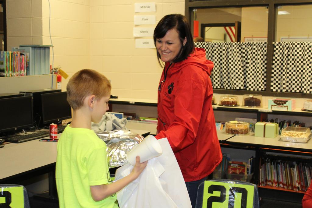 teacher giving student a cake at cake walk