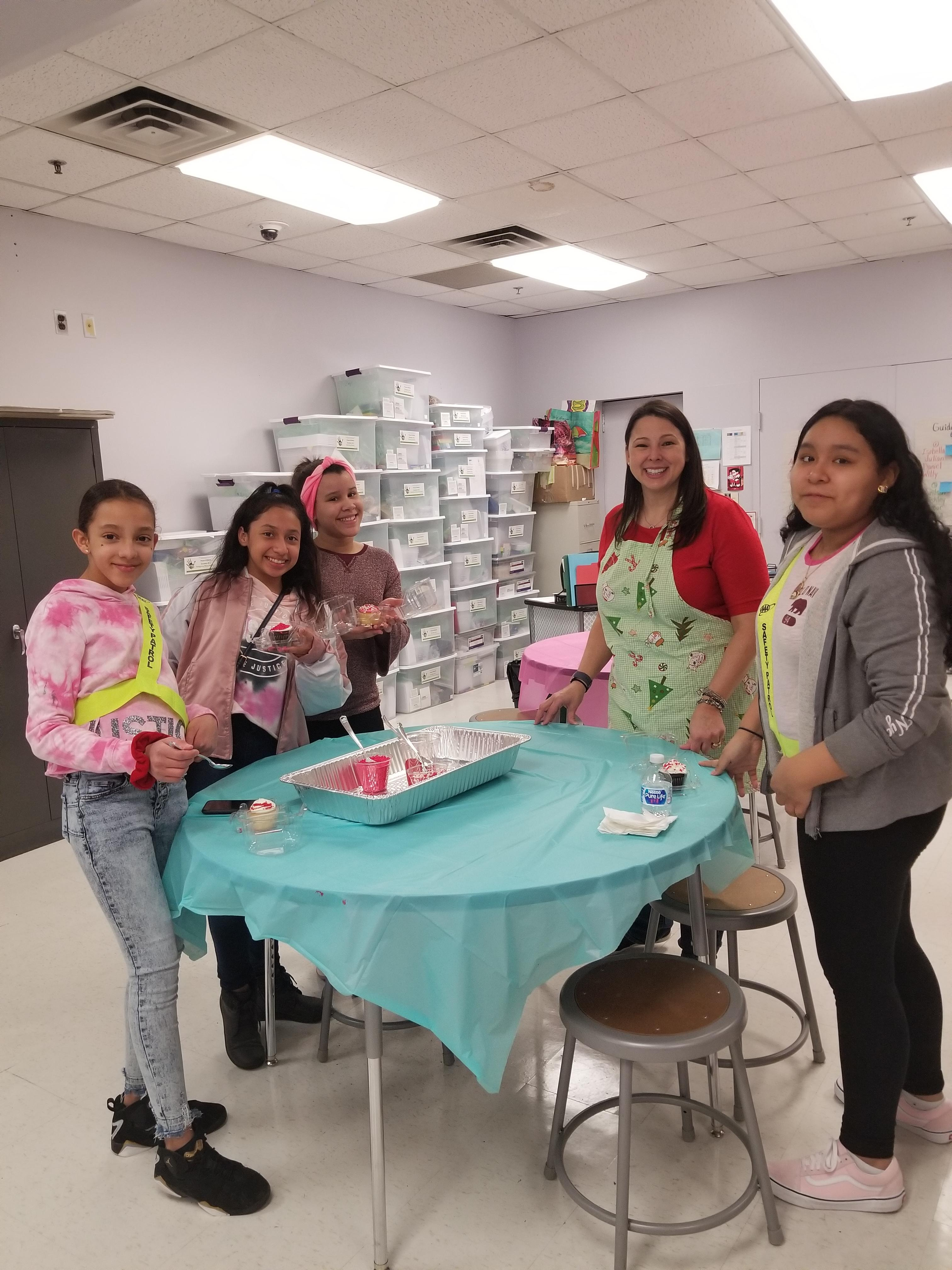 girls showing off their decorated cookies and cup cakes