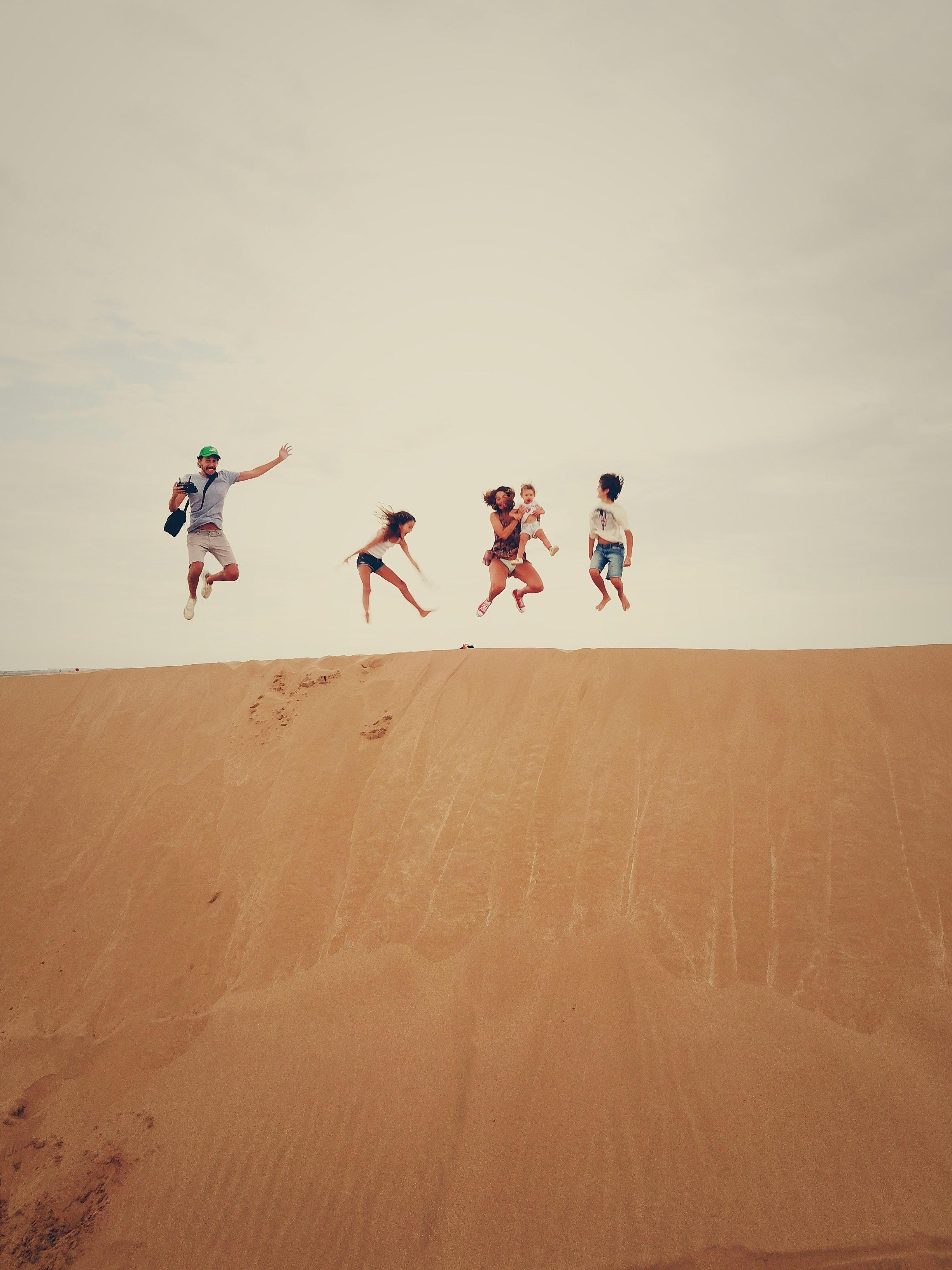 A family jumping exuberantly into the air over a sand dune