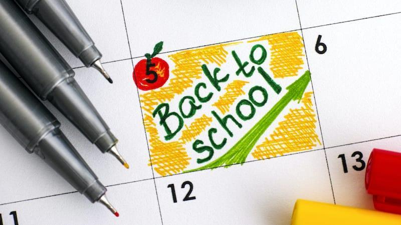 Pencils and paper with apple that says back to school
