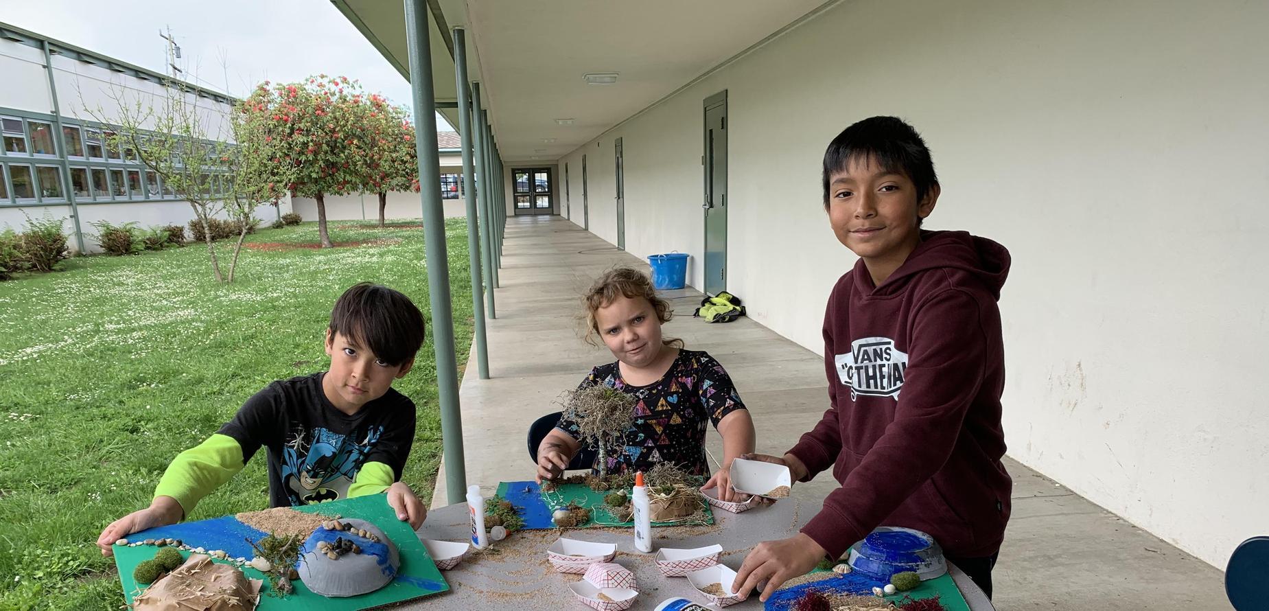 three students with Chumash village models