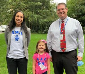 All smiles as Wilson principal Crystal Marsh and school counselor Frank Uveges pose with 2nd grader Aviva Clarke after walking to school together on Oct. 6.
