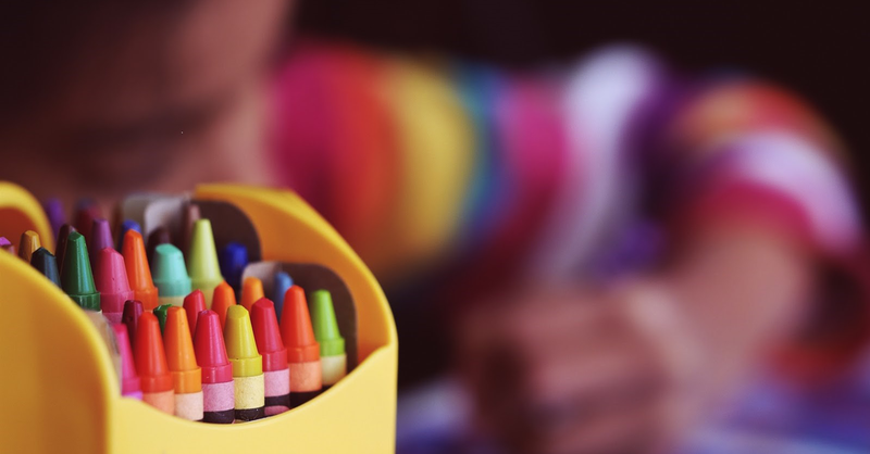Student in classroom with crayons.