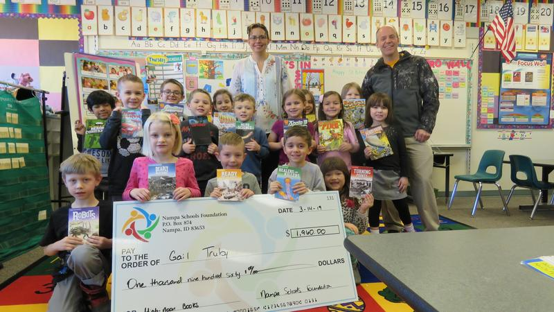 Teacher Gail Truby and Principal Steve LaBau pose with kids and a grant check.