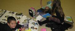 Students reading on floor with blankets and book bags