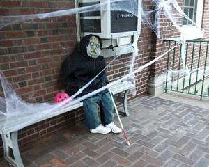On the front porch bench sits a creepy ghoul waiting to scare someone.