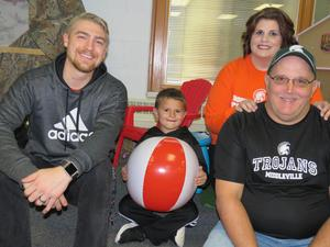 Kindergarten teacher Jacob Bultema with his student Joey Graham and Joey's parents, Dawn and Joe.