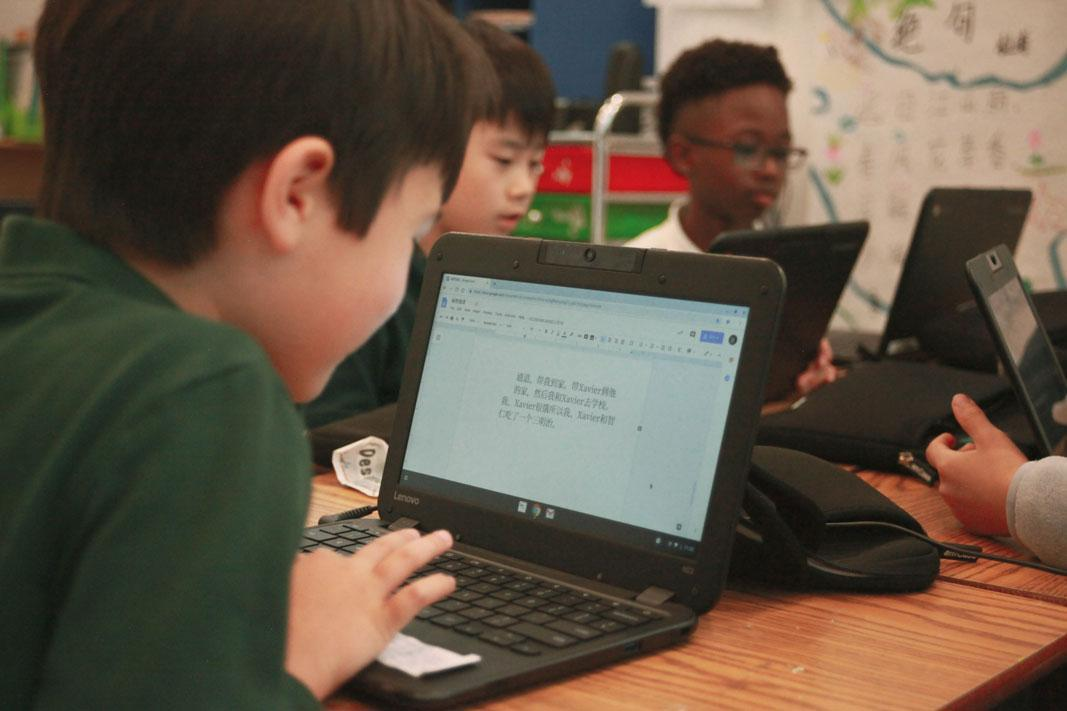 HWIS elementary student writing in Mandarin on his Chromebook